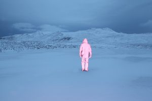 A photograph by Will Gill. A figure in a fuchsia metallic hazard suit walks into the distance of a blue toned arctic landscape.
