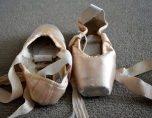 A pair of well worn pointe shoes pictured on a carpet. One with the toe pointing forward. One with the heel pointing forward.