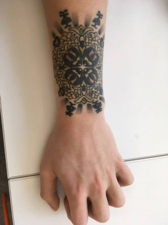 Image of gold and yellow coloured mandala tattoo with black shading on caucasian man's left outer wrist.