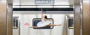 Photograph of a ballet dancer doing a jété jump in front of a stopped subway train.