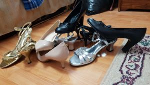 A photograph of a pile of high heel shoes