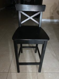 black, wooden barstool chair with a back rest.