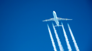 Images displays a four engine white airplane against a blue sky. The airplane is creating four contrails from each of the engines.