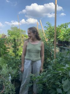 Young woman surrounded by plants in green hand knit tank top