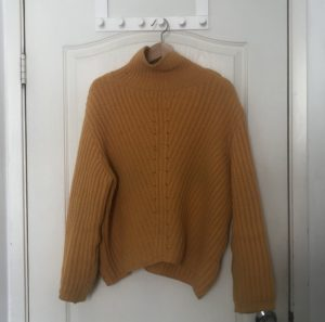 Image of yellow sweater hanging on the back of a white door