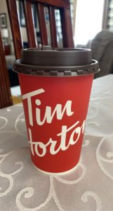 Pictured is a red Tim Hortons cup with white lettering across the middle and a brown lid.