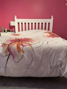 Payton Flood's bed with a wrinkled, pink and orange floral comforter.