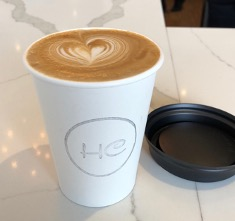 A cappuccino with a heart milk foam design. In a white cup with the lid to the right of it, on the counter. The Café's logo is stamped on the white cup in a grey colour, has the letters HC in a circle on it. The counter it is placed on is white with grey marble and there is a reflection of a chandelier on it.